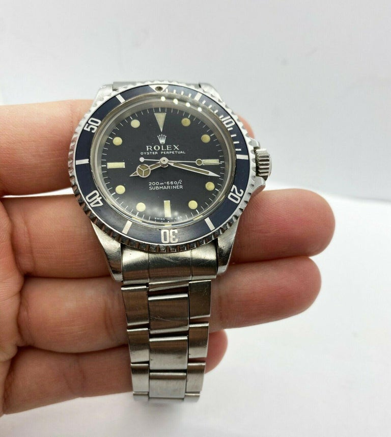 Style Number: 5513  Serial: 1607***  Year: 1967  Model: Submariner   Case Material: Stainless Steel  Band: Stainless Steel  Bezel:  Black  Dial: Black  Face: Acrylic Crystal  Case Size: 40mm  Includes:  -Elegant Watch Box -Certified Appraisal  -1