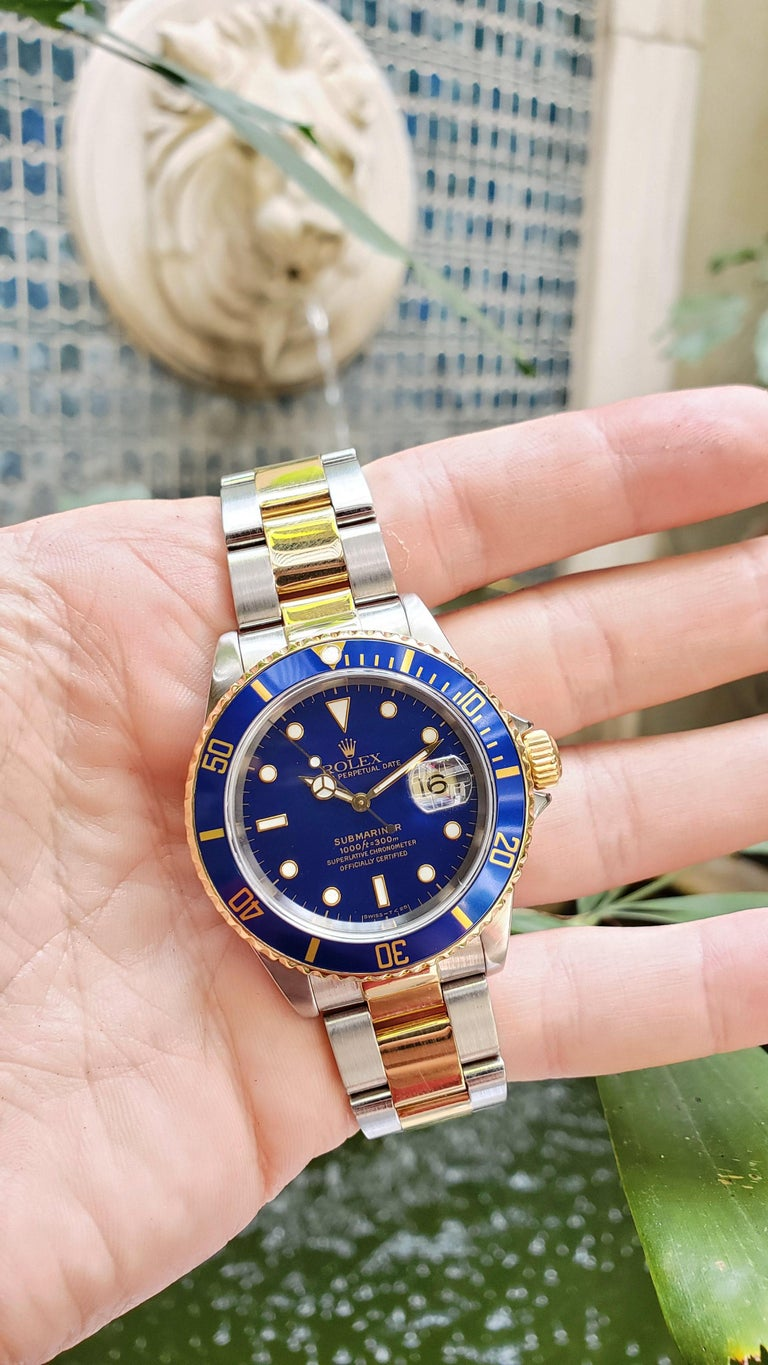Vintage Rolex Submariner, circa 1997. Stainless steel and 18kt yellow gold Submariner with blue dial and blue bezel.   Classic Rolex Sub with vintage blue color. Bracelet is tight and clean condition. All of our watches go to an Authorized Rolex