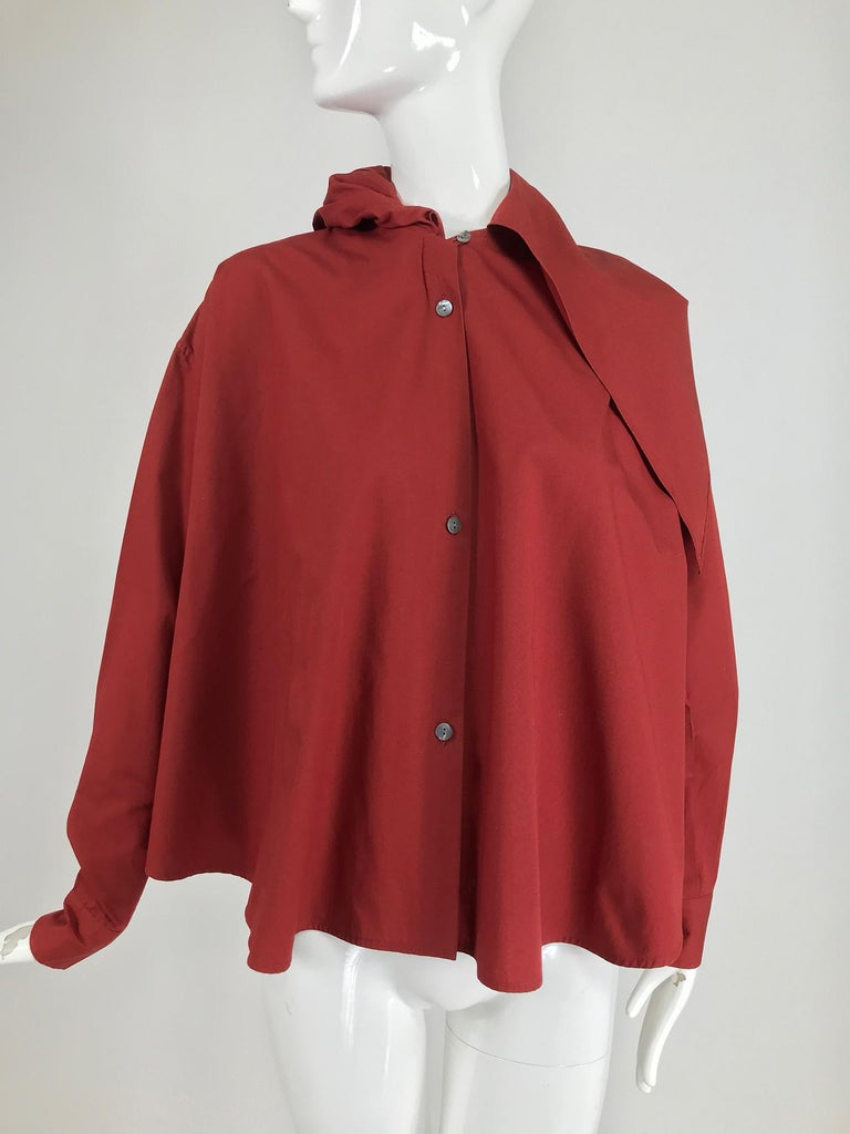 Vintage Romeo Gigli burgundy cotton oversize shirt with attached hood/scarf from the 1980s. Long sleeve shirt is full from the shoulders to the shirt tail hem, there is a box pleat at the shoulder back. Long sleeves have button cuffs. Attached at