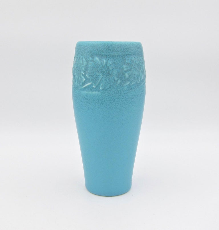 A vintage Rookwood Pottery Arts & Crafts production vase with a blue matte glaze made in 1930. This elegant American vessel is decorated with a molded band of sunflowers just below the rim.  Good condition with a small glaze loss/nick at the rim