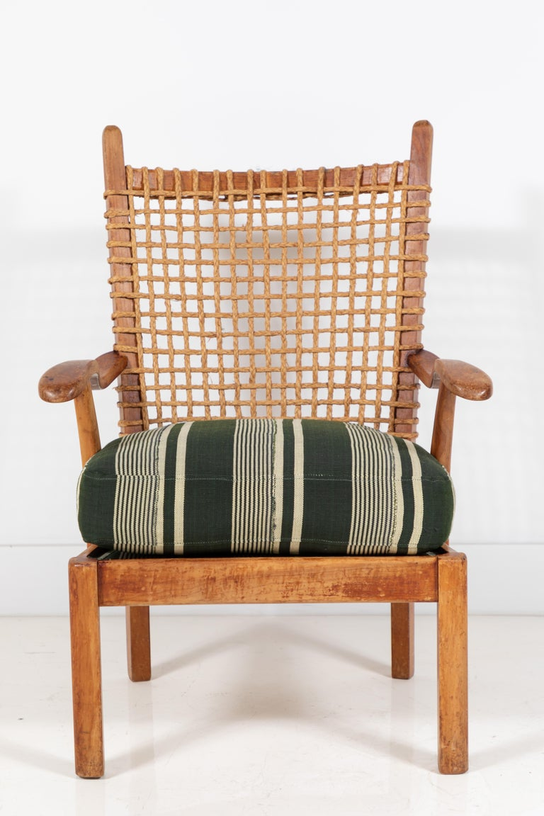 Vintage wooden arm chair with back rest made of woven rope, newly upholstered green striped seat cushion made from a one of a kind African textile.