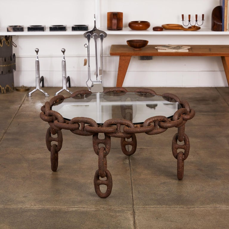 Heavy solid iron stud chain has been skilfully welded to create a perfectly symmetrical round coffee table with four legs. Glass top insets to create the table surface.  Condition: Heavy patinated iron chain. The glass looks to have been replaced
