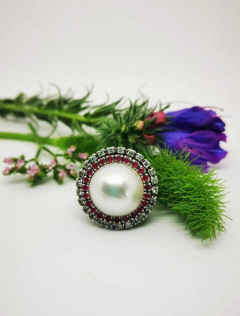 Vintage Pearl, Rubies and  Diamonds ring  This classic elegant vintage ring with a very beautiful pearl Mabe 15mm diameter surrounded by 23 rubies and 25 diamonds. Top is the ring measures 22mm by 22mm and shank measures 2mm.  Size ring US - 5 1/2