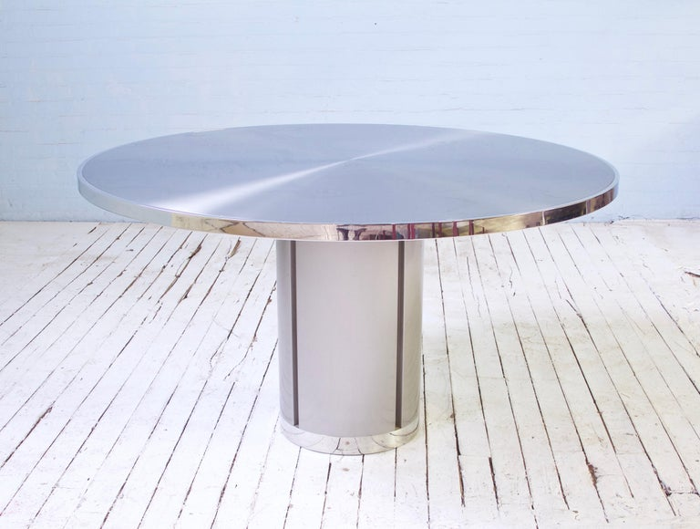 Attractive and useful pedestal-base dining table comprised of brushed aluminum, polished chrome accents, and a welded steel frame with counterweighted base. There is no bad angle on such a minimal, timeless design. Table has been photographed with a