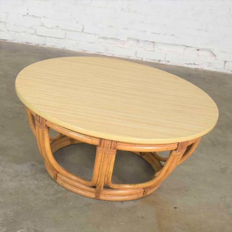 Handsome round rattan drum shape coffee table or end table with laminate top. It is in wonderful vintage condition with no outstanding flaws only normal wear for age. Laminate top may be a replacement top at some point in its life but looks