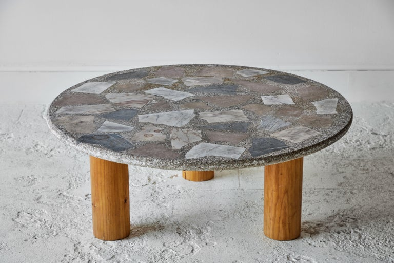 Vintage round terrazzo table sits on top of a three cylindrical legged oak base.