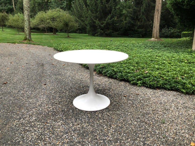 "Vintage ""Tulip"" dining table  having an aluminum base and laminate top. Wear consistent with age and use."