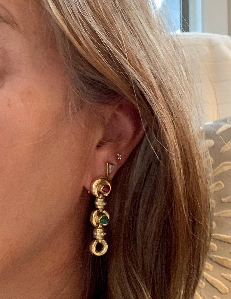 These earrings are perfect for any time of year.  They feature two 6 x 4mm oval cabochon stones in each earring; one Ruby and one Emerald.  There are ten brilliant cut Diamonds accenting the Gold between the cabochons.  The brilliant cut Diamonds