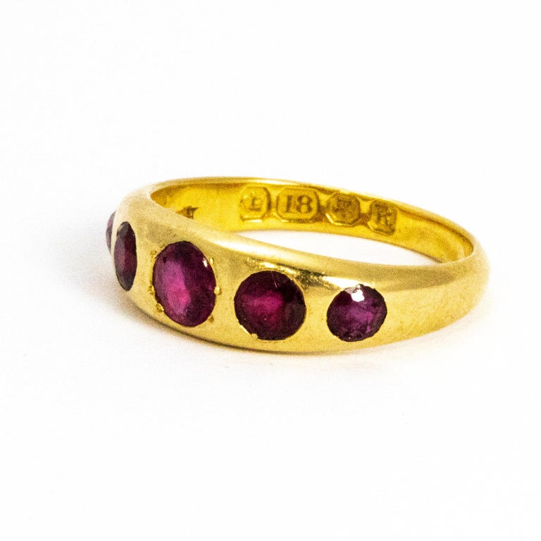 Five graduated sparkling rubies are held in this chunky 18ct gold band. The beautiful rubies are set flush in the band so the ring is very stream lined and smooth. Made in London, England.  Ring Size: K 1/2 or 5 1/2 Band Width: 4mm