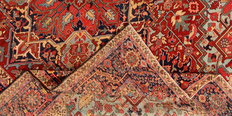 Vintage 1920 Persian Heriz carpet with a rust field and central medallion design, in blues with earth tone accents. Measures: 11.05 x 15.03.