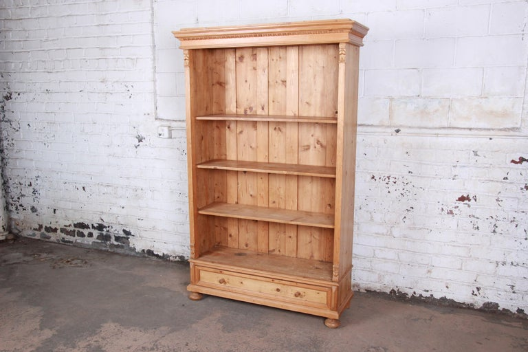 A gorgeous primitive solid pine bookcase. The bookcase features beautiful carved wood details and nice knotty pine wood grain. It offers ample room for storage and display, with three open shelves and a single dovetailed drawer below. The bookcase