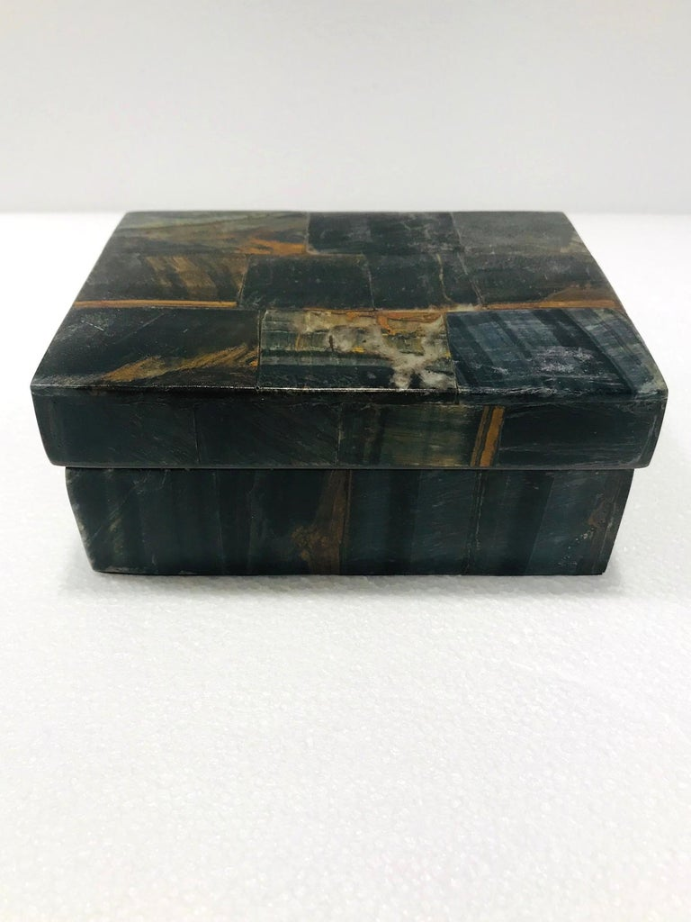 Organic Modern decorative box in semi-precious blue tiger eye stone, also known as falcon's eye. Tessellated design featuring inlays of multicolored stone in hues of brown, black, blue, rust, and dark green. Interior box is made of palmwood. All