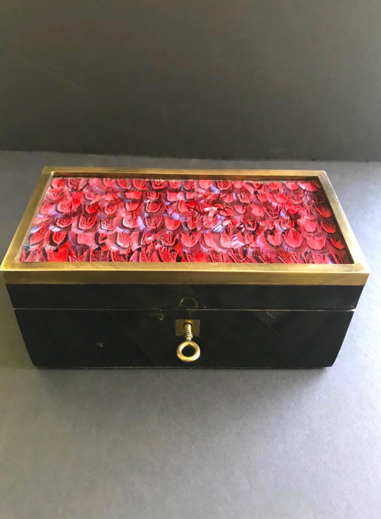 Exquisitely handcrafted decorative box or jewelry box. Comprised of lacquered pen shell with geometric mosaic patterns in hues of black. Box has bronze trim accent and exotic bird feathers in vibrant red. Fitted with bronze mount and key, and