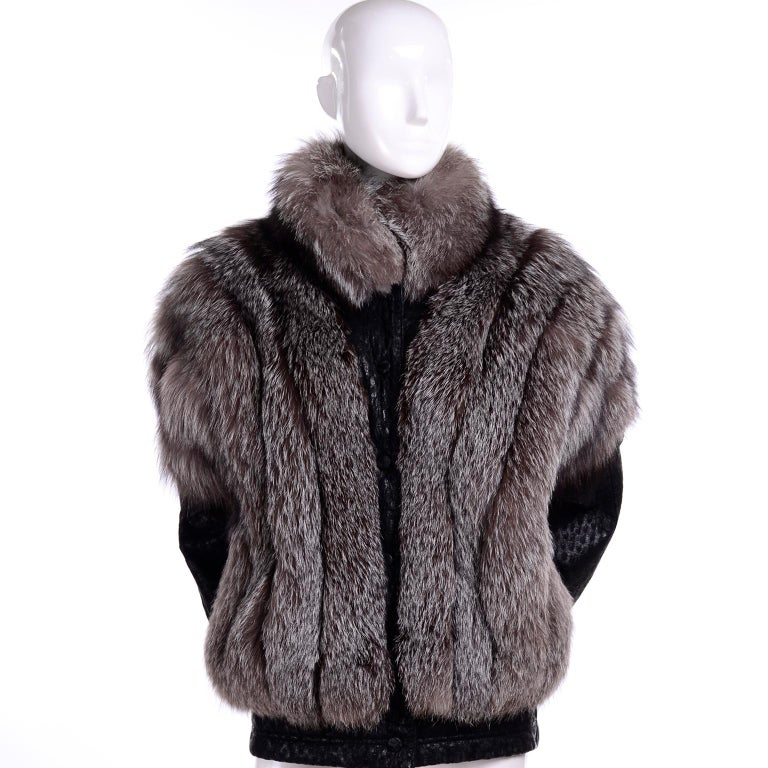 This vintage 1980's jacket is from Saga Fox and is really like getting two pieces in one!  This luxurious vintage coat has a grey fox fur body and removable black ostrich embossed leather sleeves and ostrich embossed leather trim. The jacket snaps