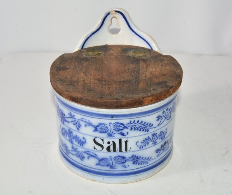 The vintage flow blue and white canister is labeled Salt. It has a wood hinged lid and a hole for hanging.