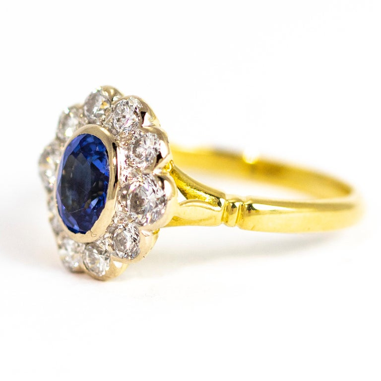 A large oval medium hue blue sapphire sits at the centre of a hoop of bright, clean old European cut diamonds which measure approximately a total of 1carat. The back of the setting is modelled into a sweet flower motif and all is made of 18ct