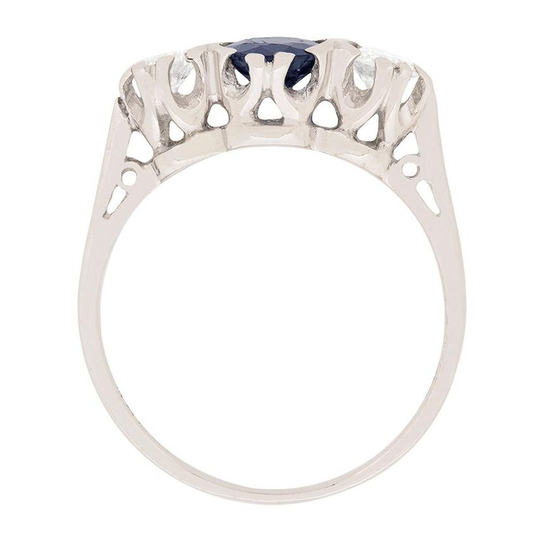 This three stone ring features a sapphire in the centre which is a a dark blue. It is set in between two round brilliant diamonds, each weighing 0.35 carat. The sapphire weighs 0.70 carat. The two diamonds are H in colour and SI in clarity. All the