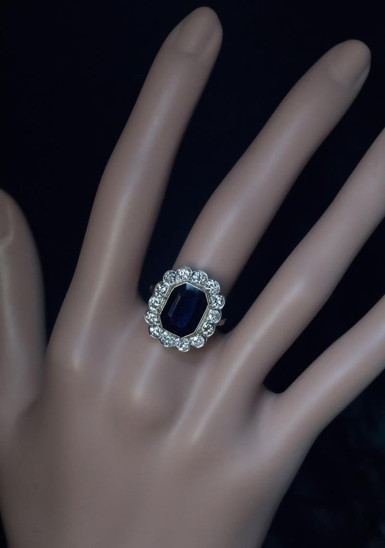 Circa 1930s-1940s  This Art Deco era engagement ring is crafted in 14K yellow and white gold. The ring is bezel-set with a step cut midnight blue sapphire surrounded by diamonds.  The sapphire measures 11.51 x 8.70 x 3.90 mm and is approximately 4
