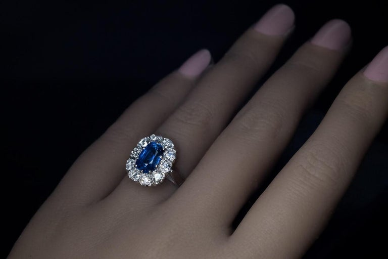 European, circa 1950 The ring is crafted in white 18K gold. It is centered with a cushion cut genuine sapphire measuring 9 x 5.9 x 4.9 mm. The sapphire is surrounded by pre-1900 chunky old mine cut diamonds (G-H color, VS1 – SI1 clarity). Estimated