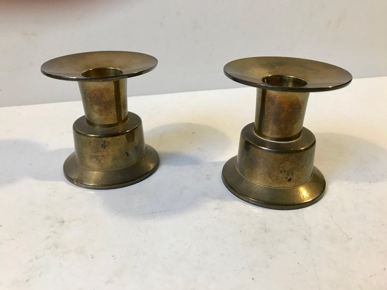 A set of 2 brass candlesticks. They are hybrid meaning that one side can be fitted with regular sized candles and the other with tea lights. Manufactured in Grillby, Sweden during the 1960s in a style reminiscent of Torben Ørskov and Pierre Forsell.