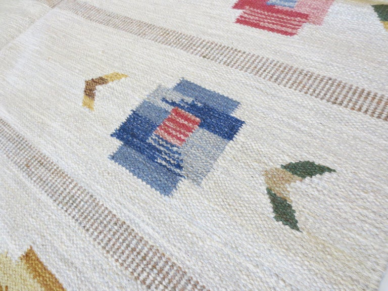 This is a vintage Scandinavian Kilim rug woven circa 1950s with quite a beautiful composition. It features an elegant display of floral motifs placed on the perimeter, like a wreath of pansies. A subdued background of gray blocks with bands of