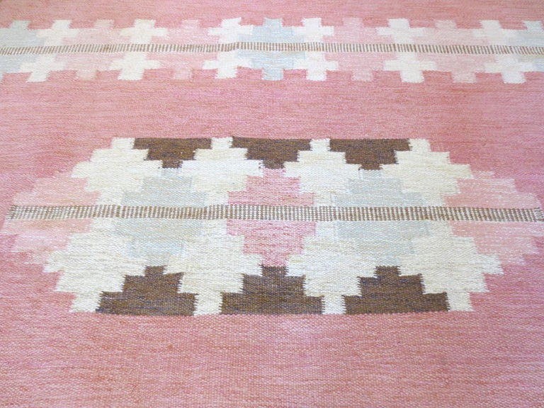 This is a Scandinavian flat-woven rug from the mid-20th century. It is signed by the designer. The color palette comprises of gentle shades of pink, icy blue, ivory, and brown in complementary geometric shapes that alternate in bands. All the