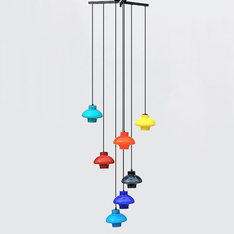 Scandinavian, 1960s cluster or cascade pendant light with staggered, multicolored lamp shades suspended from a metal tripod frame (flush mount). There are seven shades in bold colors: blue, green, black, yellow, orange and red. The multicolored