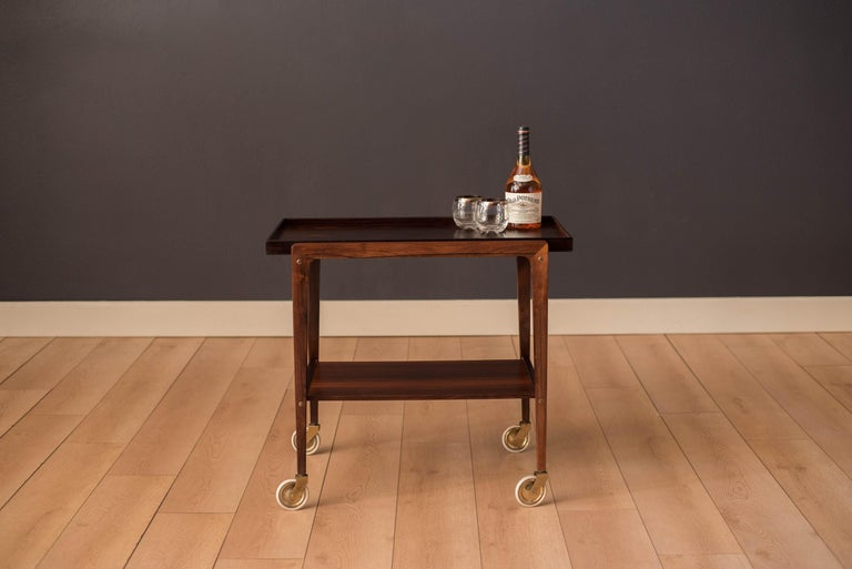 Mid-Century Modern bar cart in rosewood, circa 1960s. Features a removable tray top with dovetail construction supported by a sculptural frame with exposed bridal joints. This piece includes two-tier storage and rolls on original casters for easy