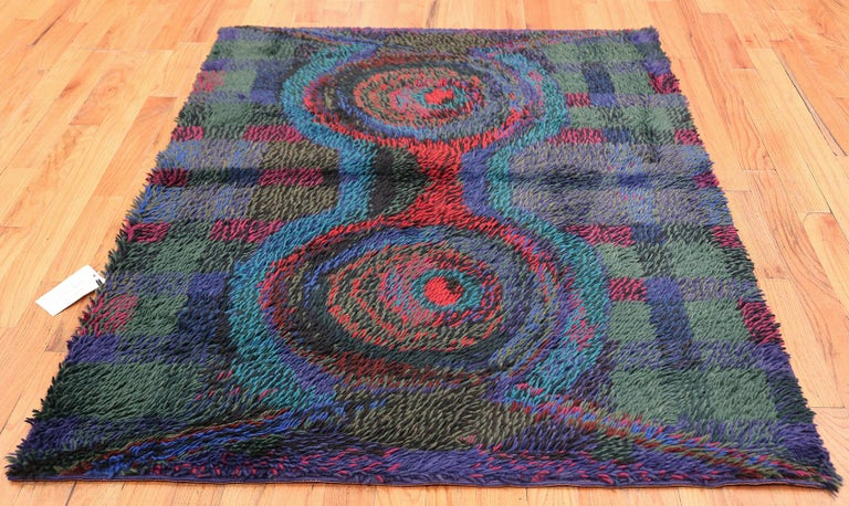 Vintage Scandinavian Rya rug by Ritva Puotila. Here is a highly unique and intriguing vintage carpet - a vintage Rya rug that was woven in Scandinavian during the middle years of the 20th century. Boasting a fascinating color pallet and a compelling