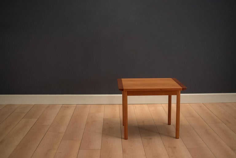 Mid-Century Modern square end table by Westnofa of Norway in teak. Features solid teak curved edges and linear dowel legs. This piece functions as a side or occasional table.     Offered by Mid Century Maddist