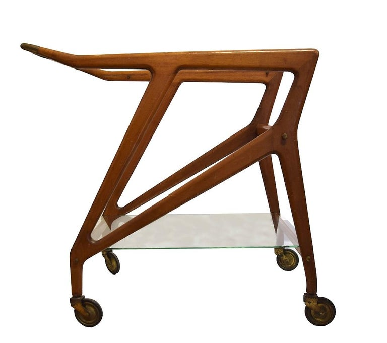 This vintage serving cart is an elegant piece of design furniture manufactured by Angelo De Baggis in the 1950s very likely on a project by Ico Parisi.  Wooden chariot with two glass shelves. A clean and refined design.  Dimensions: cm 76 x 90 x