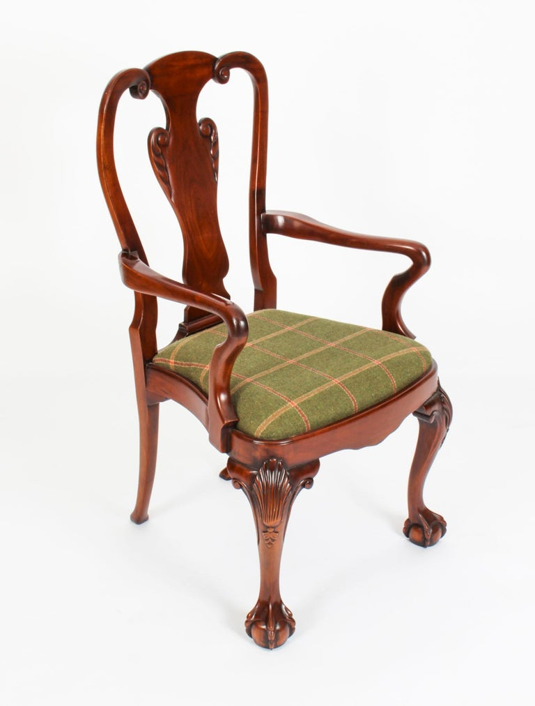 An absolutely fantastic set of twelve vintage Queen Anne Revival dining chairs, dating from the mid 20th century.  The set comprises ten side chairs and a pair of armchairs. They have been masterfully crafted in beautiful solid mahogany and the