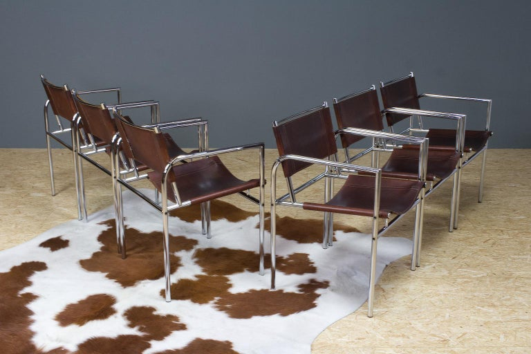 Great European vintage set of 6 dining room chairs in brown leather and chromed metal, tubular frame with armrests. 1960s design in manner of Charlotte Perriand or Martin Visser, origin unknown, no label present. The chairs are well detailed, and