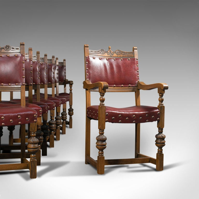 This is a vintage set of 8 dining chairs. An English, quality oak and leather suite in Carolean revival taste, dating to the mid-20th century, circa 1950.  Wonderfully regal dining room set Pair of dashing carvers for the heads of the