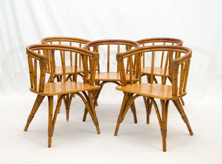 Set of five Heywood Wakefield captains chairs from their Ashcraft line which was made to look like the legs and backs were rattan, with paper cord wrapping at the fronts of the arms as well as the legs. The wrappings were decorative accents. These