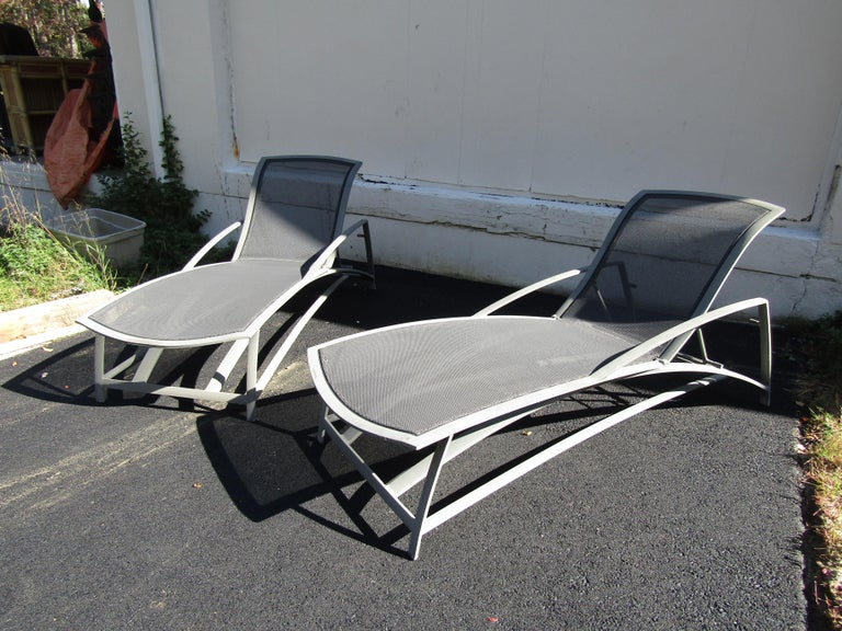 A beautiful set of aluminum outdoor furniture by Jordan Brown. This set includes a glass top coffee table, two lounge chairs, a dining table, four dining chairs, a set of two nesting tables, and two adjustable chaise lounges. Extremely stylish and
