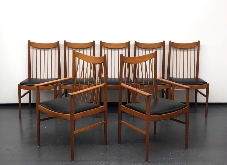 Original set of seven dining chairs by Arne Vodder for Sibast, Denmark. Solid wood construction with original black vinyl seating. There are two arm chairs and five side chairs. Each chair is marked with the Sibast foil label.