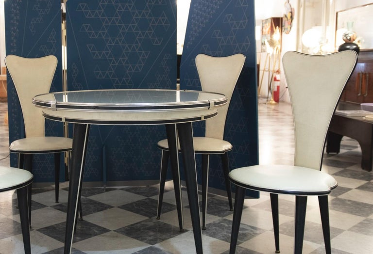 Vintageset of table and chairs is a design furniture realized by Umberto Mascagni in the 1960s.  Wood, viny-leather cream and black, metal and glass.  Table dimensions: cm 78 x 90 x 90. Chairs dimensions: cm 98 x 40 x 45.  Excellent