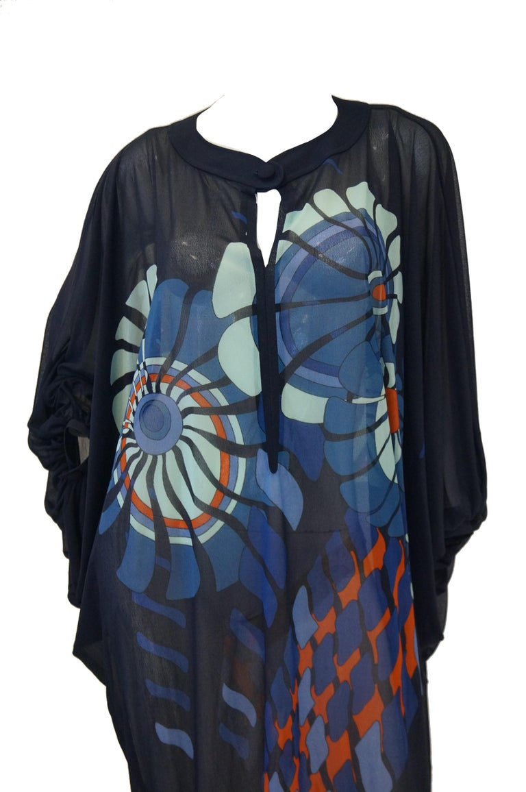 Amazing sheer black caftan featuring an incredible optical art print spread across the front and back of the dress. The dress is maxi length, with batwing sleeves and rounded shoulders. The neckline is rounded, with a slit that drops down that