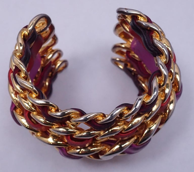 "This vintage Chanel runway cuff bracelet has five rows of interweaved lambskin leather in a gold tone and polychrome setting.  The leather colors are lavender, fuchsia, coral and burgundy.  In excellent condition, this cuff is signed ""Chanel 26 Made"