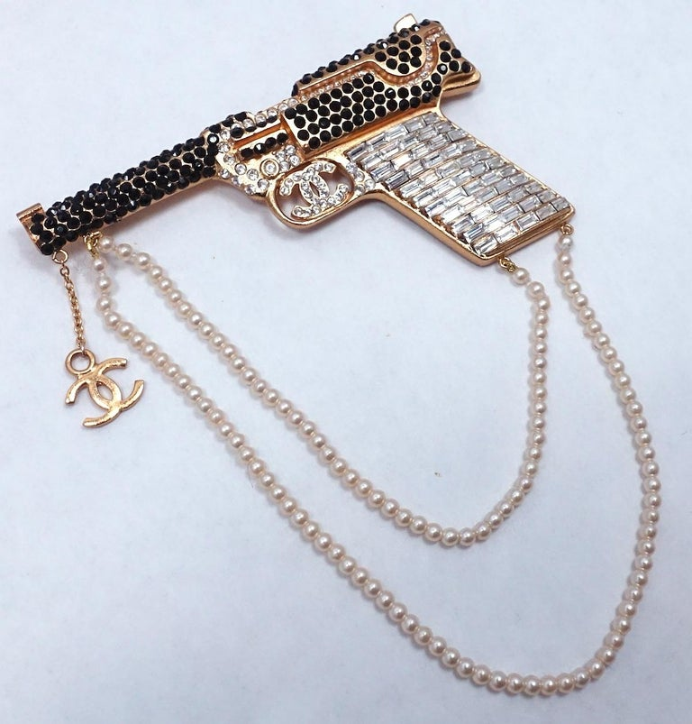 This vintage Chanel runway pistol brooch is one of the most sought after Chanel cuff bracelets. It has crystals throughout with two rows of faux pearls hanging downward and the Chanel CC logo at the end of the pistol.  In excellent condition, this