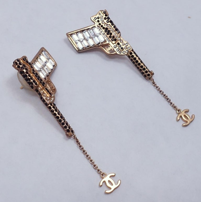 "These vintage signed Chanel runway pistol earrings match the Chanel pistol brooch listed in this update. They have crystals, faux pearls with the ""CC"" logo at the end. These clip earrings measure 1"" x 3"" and are from the 2001 Autumn Collection.  In"
