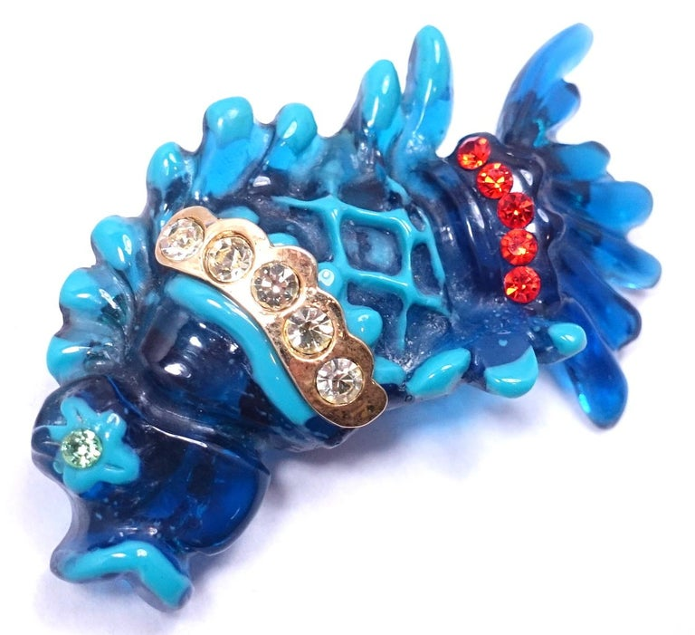 """This impressive vintage signed Christian LaCroix jeweled fish brooch has different shades of blue with clear and red crystal accents …  in a gold tone setting.  This brooch measures 2-1/4"""" x 3-1/2"""".  In excellent condition, it is signed """"Christian"""