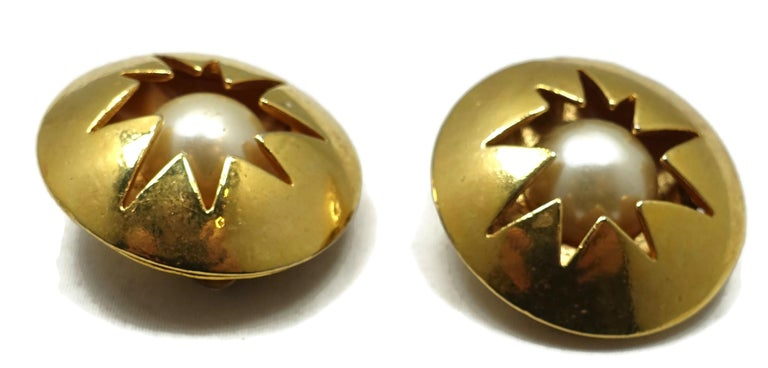 """These vintage signed Dolci Vita round earrings have a faux pearls center encased within a star design in a gold tone setting.  In excellent condition, these clip earrings measure 1-1/4"""" and are signed """"Dolci Vita""""."""