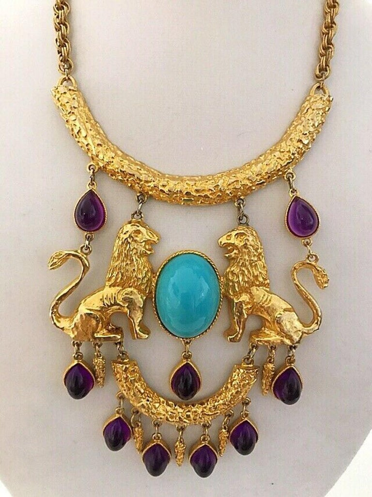 Spectacular Donald Stannard Iconic Twin Lions bib Necklace. Fabulous massive Book Piece Necklace adorned with a large oval shaped cabochon Turquoise Lucite and nine dangling tear drop shaped cabochon Amethyst Lucite; set in ornate gold plated