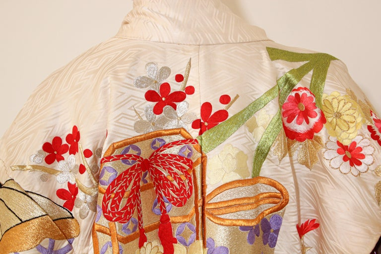 A vintage midcentury ivory color silk brocade collectable Japanese ceremonial wedding kimono. One of a kind handcrafted fabulous museum quality ceremonial piece in pure silk with intricate detailed hand-embroidery throughout accented with floral