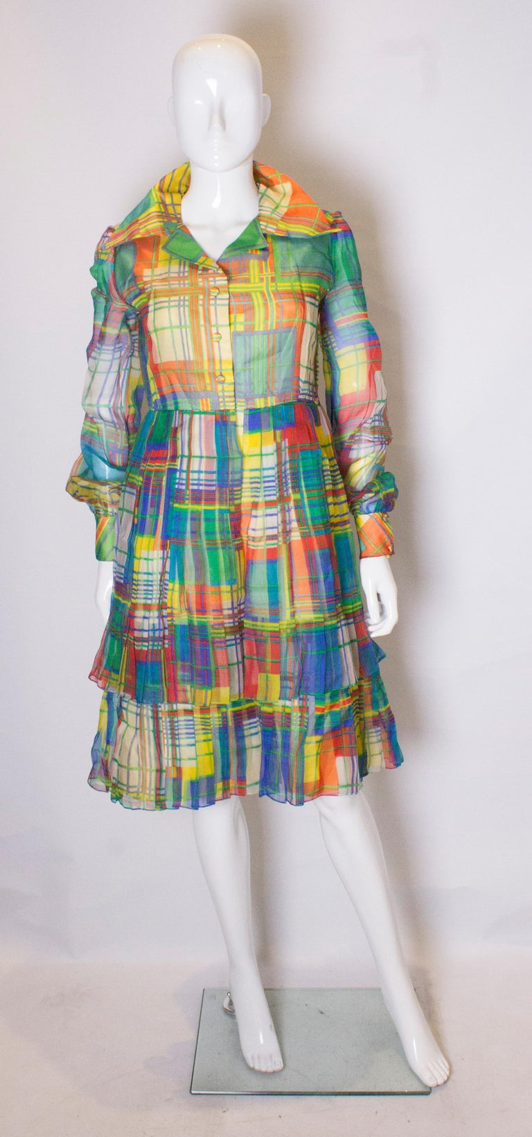 A head turning vintage dress by Nettie Vogue London. The dress is in a wonderful multicoloured print with layers of pleating on the skirt . It has popper opening  at the front and on the cuffs.