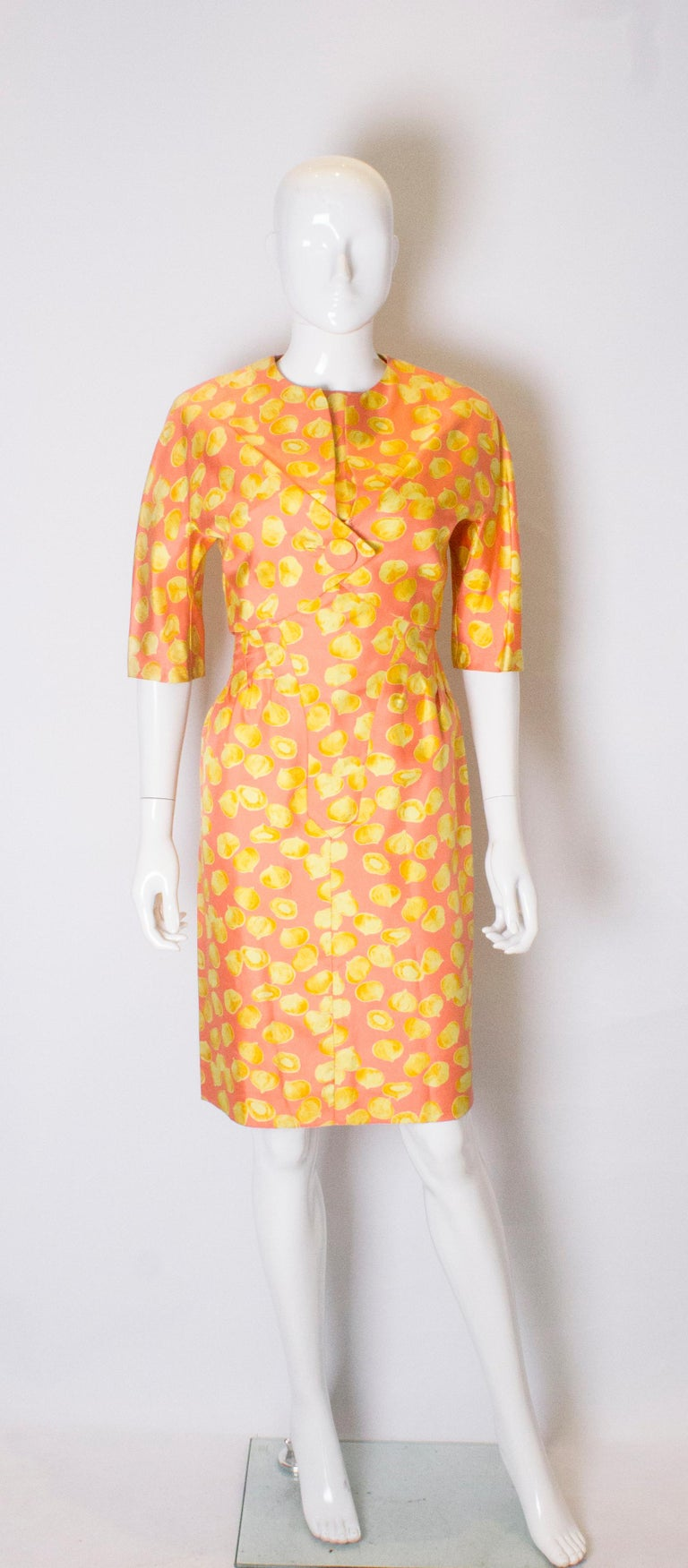 A great silk cocktail dress and jacket in an interesting and unusual garlic print .  The dress has 11 fabric covered buttons at the front and is tailored with a round neckline. It has a central back zip , 4 '' slit at the hem, and a 4 1/2'' hem.  It