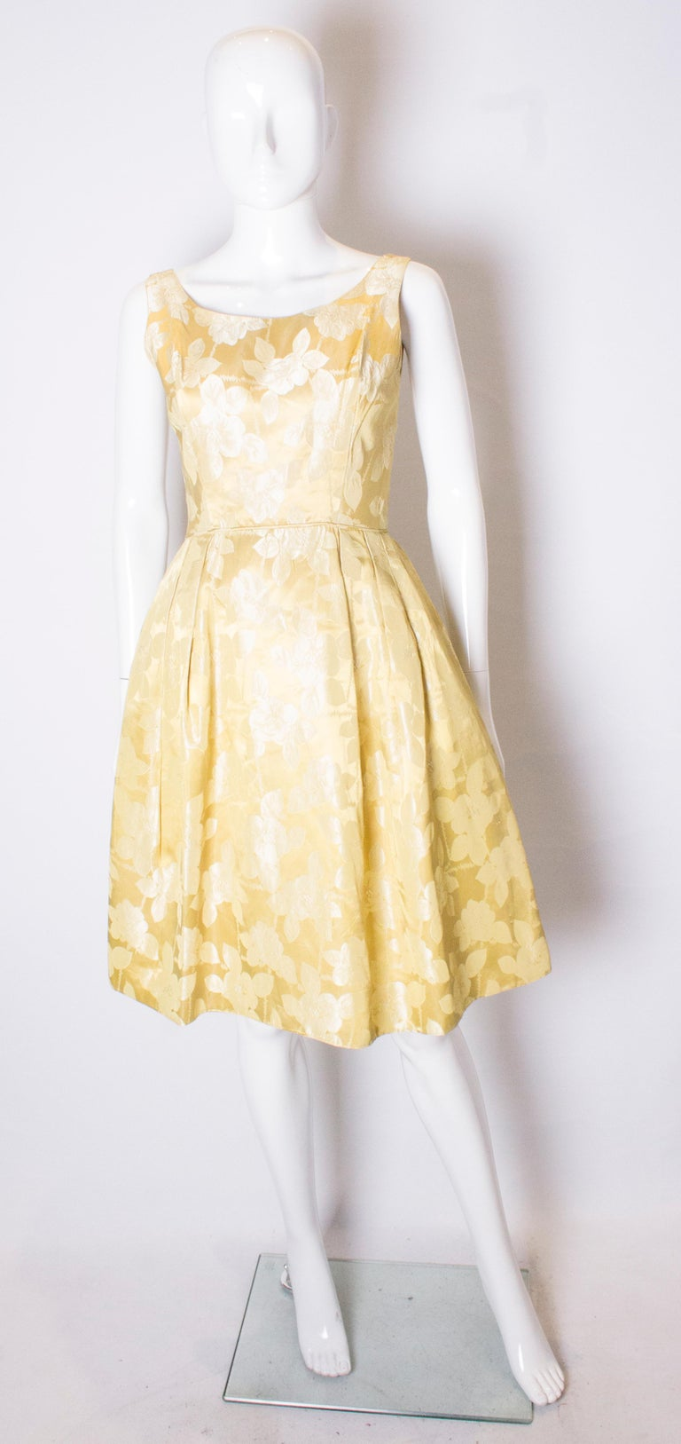 A chic vintage cocktail dress in a pretty yellow/gold colour . The dress has a scoop neckline, front and back with small gathering at the waist. It is fully lined with a central back zip and an net underskirt.