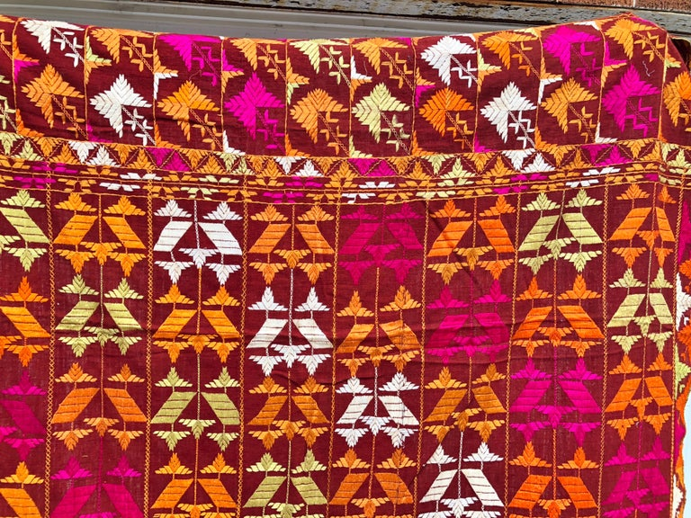 Vintage silk embroidered Phulkari wedding shawl from Punjab, India. The shawl is handwoven cotton khadi cloth that is hand embroidered with vibrant silk threads. Made by relatives of the your girl for her wedding and other special occasions. The